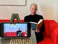 Bild genom en filmande kamera på en bibliotekarie i en soffa som läser en bok