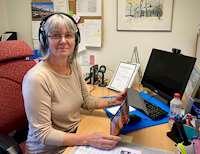 Porträttbild på Marita Olofsson vid sitt skrivbord