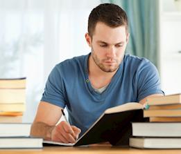 Studerande man läser ur en bok och skriver i ett anteckningsblock.