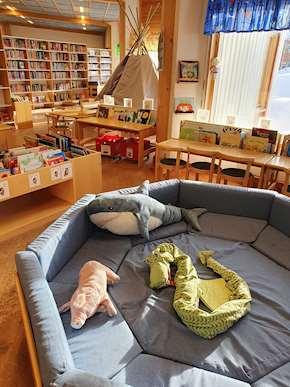 Foto på barnavdelningen på Sorsele bibliotek med många böcker, den blå pölen och gosedjur i förgrunden och tältkåtan i bakgrunden tillsamma