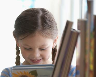 Flicka som läser en boks baksida.