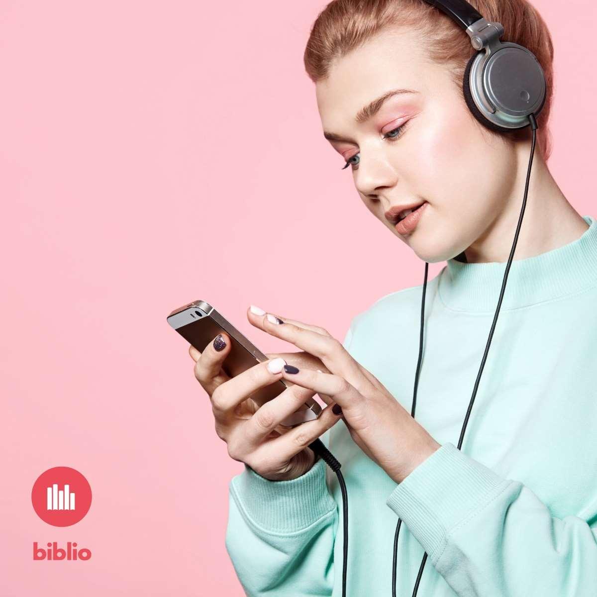 Bilden visar en person som lyssnar på något i hörlurar som är kopplade till en mobiltelefon. En logotyp för Biblio finns också med.,
