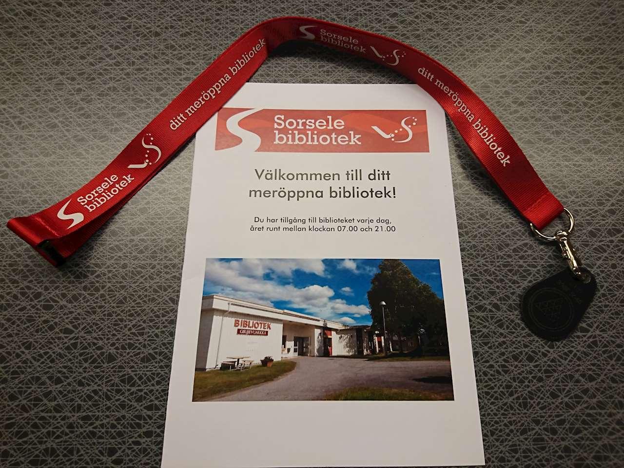 Foto på ett nyckelband och en broschyr med information om meröppet på Sorsele bibliotek