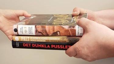 Händer som håller i tre böcker och räcker över dem till någon annans händer.